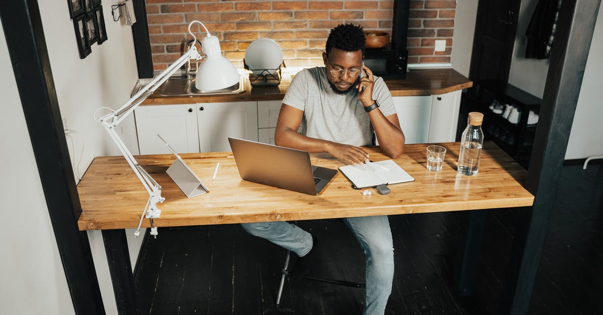 A man using a laptop computer sitting on top of a wooden table